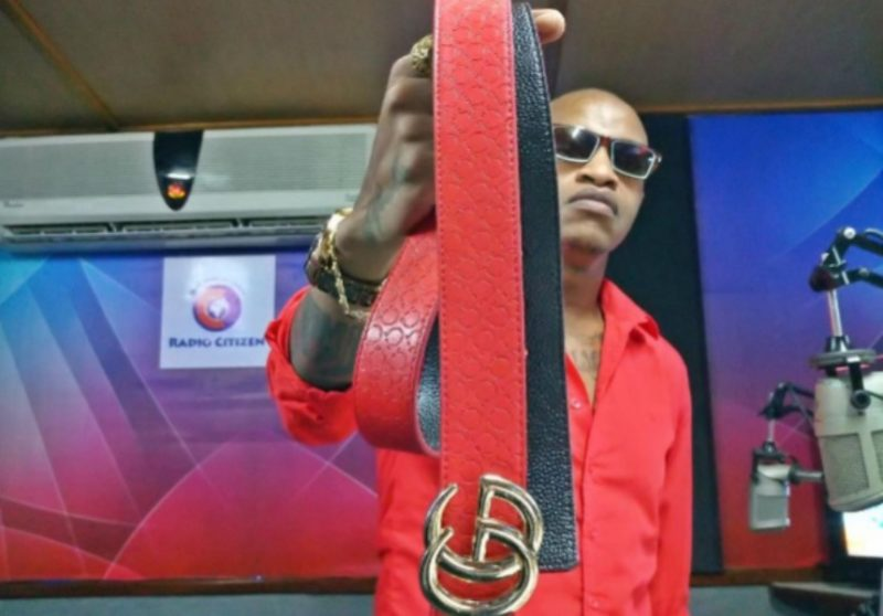 Prezzo holding up a red Gucci belt