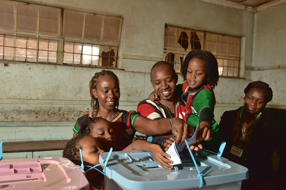 Boniface Mwangi with wife Hellen Njeri Mwangi and their children casting their votes via Facebook