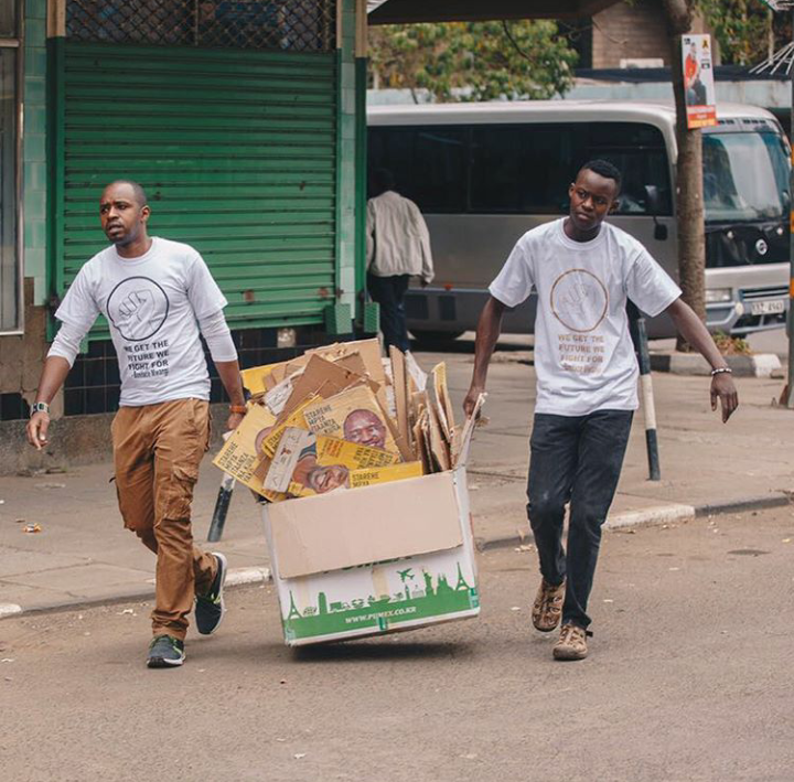 Boniface Mwangi(Left) clearing his posters off the streets with one of his friends via Instagram