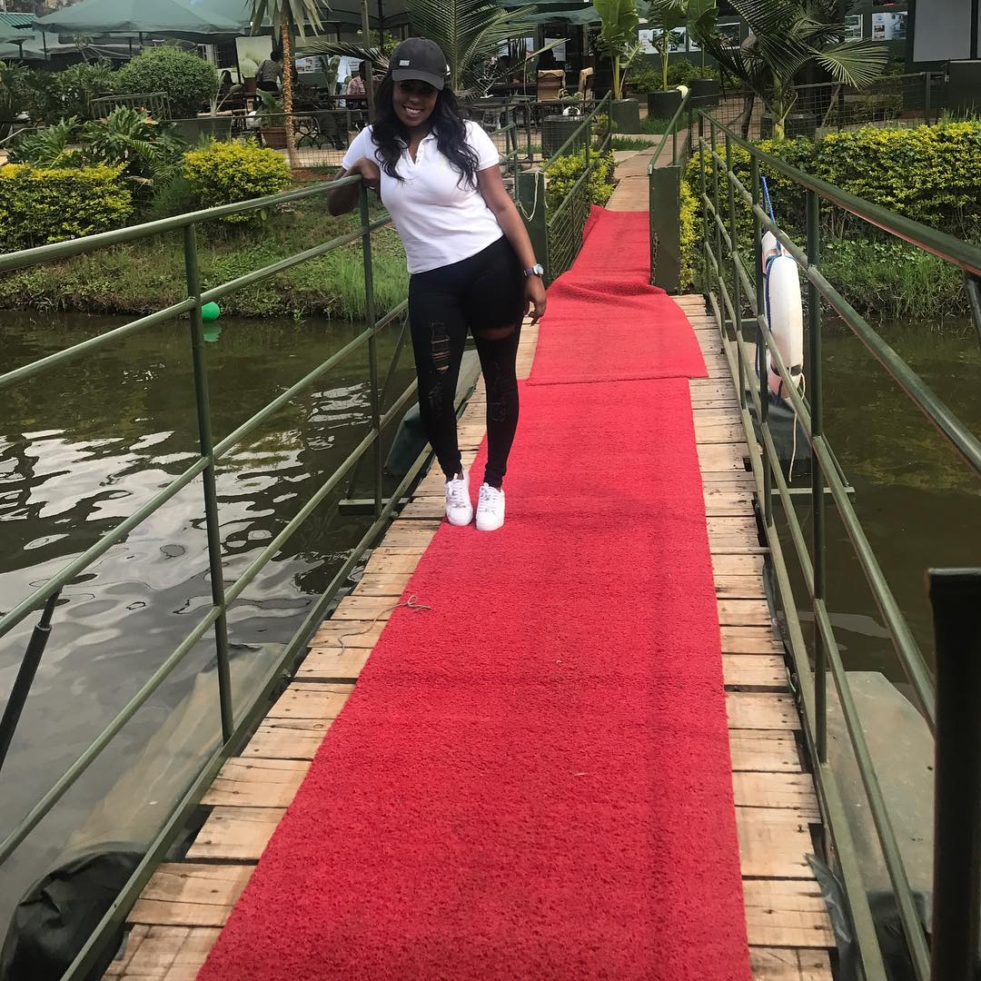 Lillian Muli looking good in white T-shirt, black jeans with white Stan Smith sneakers