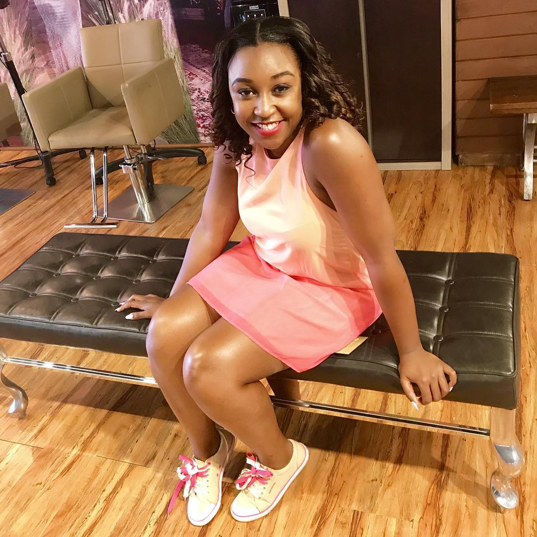 Betty Kyallo sitting on chair in pink
