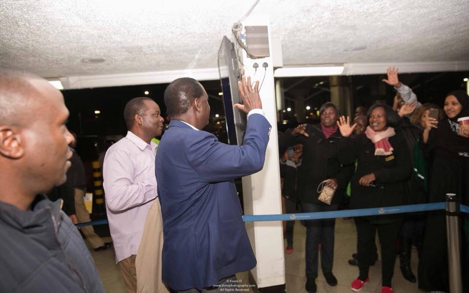 Raila waves at his supporters at JKIA