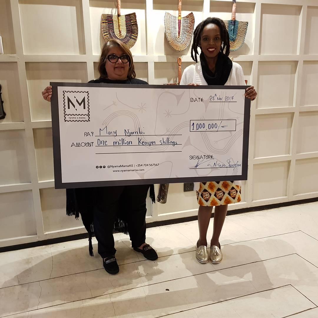 Nyama Mama representative issuing Njambi Koikai a dummy check of a million shillings. photo credit: Instagram/jahmbykoikai
