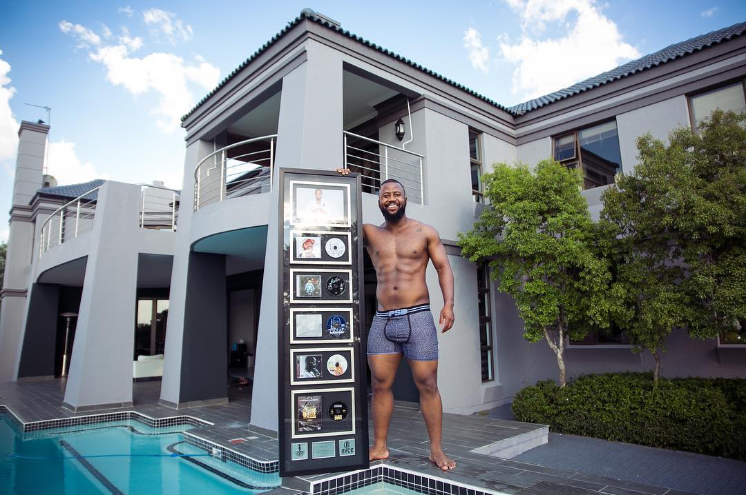 Cassper Nyovest showing off his records that sold cumulatively 10 million