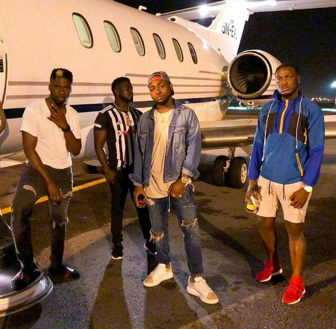 Davido posing for a photo outside the jet before take off