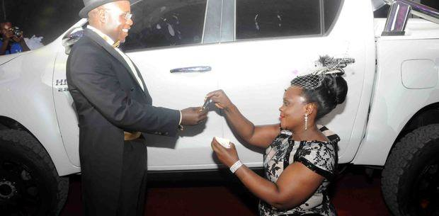 Ruth Ssebalamu kneels as she presents her husband with keys to a brand new Toyata Hilux that she bought him. Photo/Courtesy